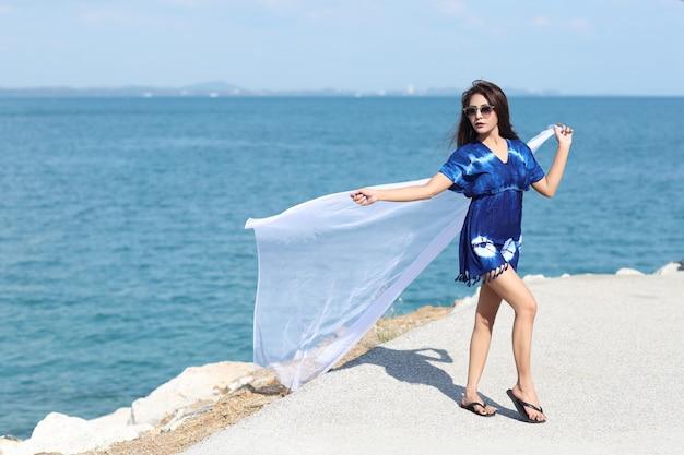 Piękna azjatykcia kobieta trzyma białą tkaninę i cieszy się wakacje na plaży