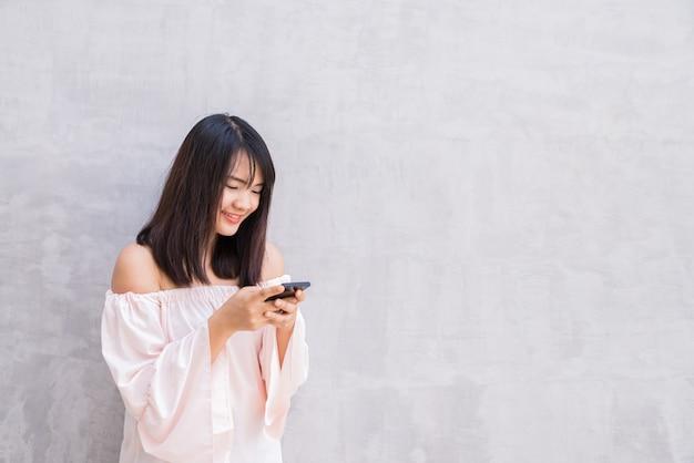 Piękna azjatykcia kobieta używa telefon komórkowego, nad betonową ścianą