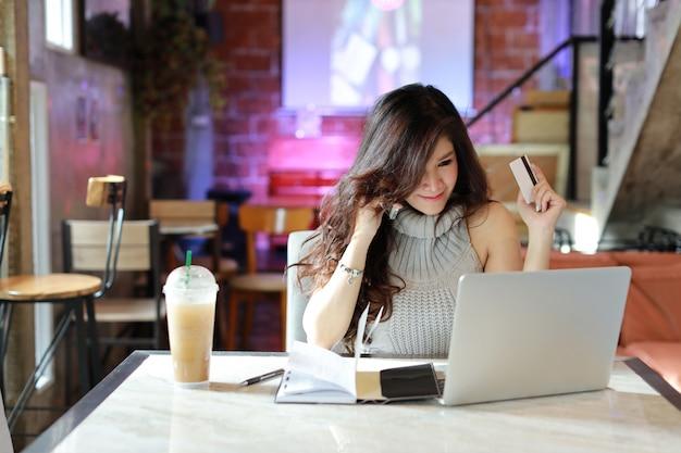Piękna azjatykcia kobieta w przypadkowym smokingowym zakupy i online zapłata na komputerze