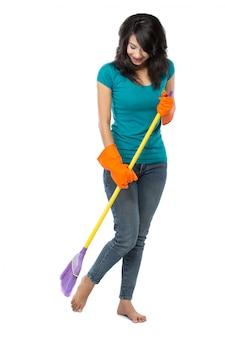 Piękna azjatykcia kobieta w rękawiczkach, zamiata podłoga z miotłą