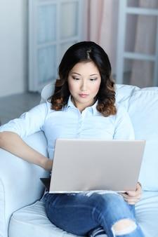 Piękna azjatykcia kobieta z laptopem w domu