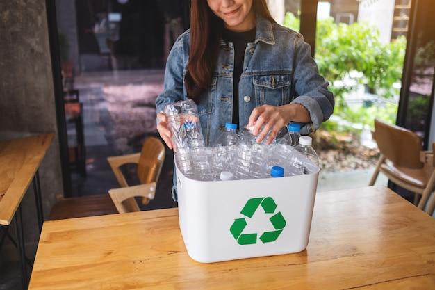 Piękna azjatykcia kobieta zbiera i segreguje śmieciowe plastikowe butelki do recyklingu w domu na śmieci