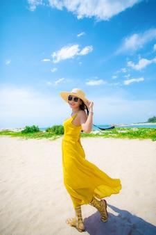 Piękna azjatykcia młoda kobieta jest ubranym kolor żółty suknię relaksuje na lata vacaiton plaży