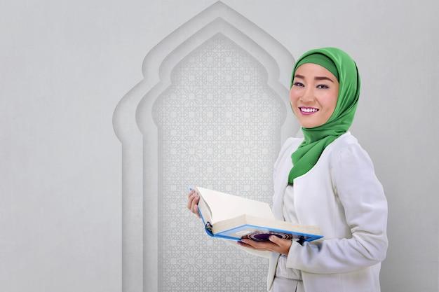 Piękna azjatykcia muzułmańska kobieta czyta koran