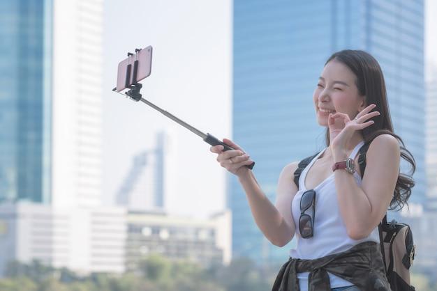Piękna azjatykcia solo turystyczna kobieta bierze selfies na smartphone w miastowym miasta śródmieściu. wakacyjna podróż w lecie.
