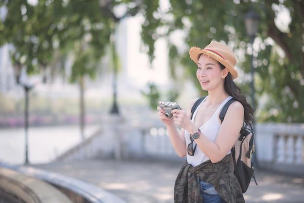 Piękna azjatykcia solo turystyczna kobieta cieszy się brać fotografię retro kamerą przy turystycznym zwiedzającym punktem.