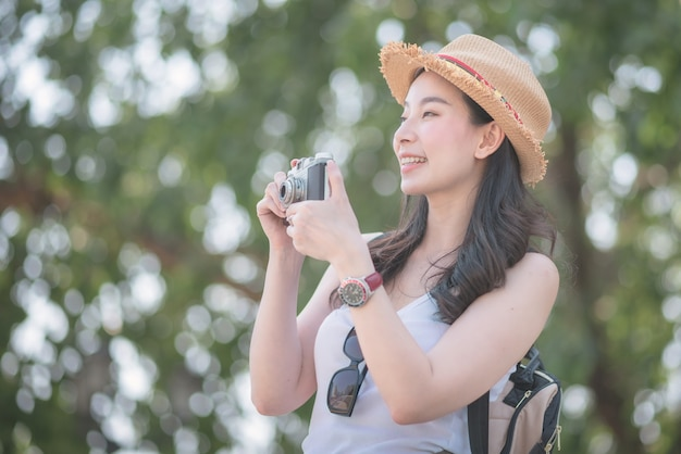 Piękna azjatykcia solo turystyczna kobieta cieszy się brać fotografię retro kamerą przy zwiedzającym punktem.