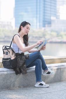 Piękna azjatykcia solo turystyczna kobieta patrzeje mapę szuka dla turysty zwiedzającego punktu.