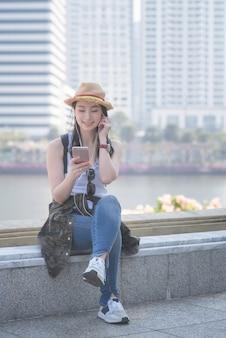 Piękna azjatykcia solo turystyczna kobieta relaksuje słuchanie muzykę na smartphone i cieszy się