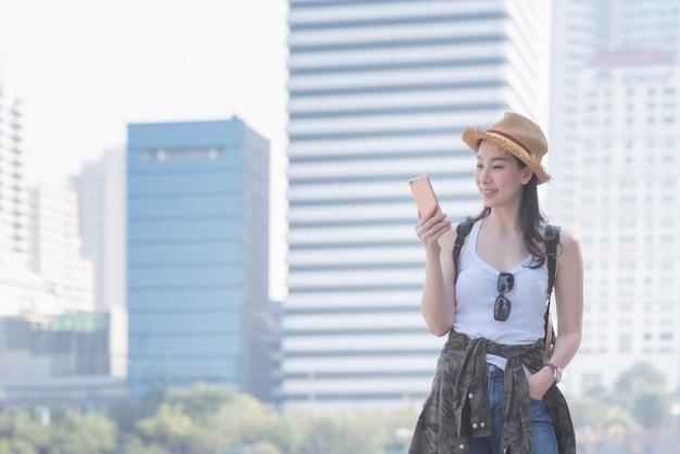 Piękna azjatykcia solo turystyczna kobieta uśmiechnięta i patrzeje telefon komórkowego