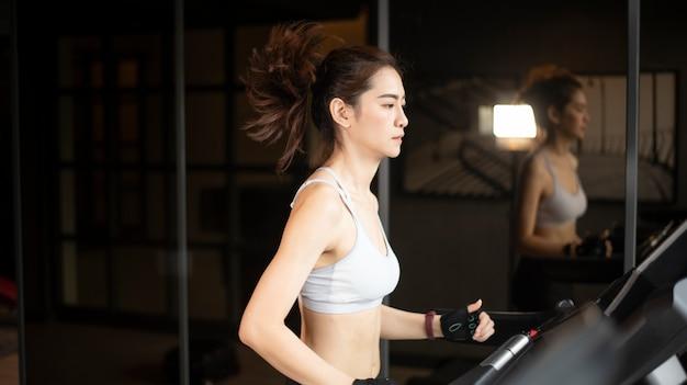 Piękna azjatykcia sport kobieta biega na karuzeli w gym