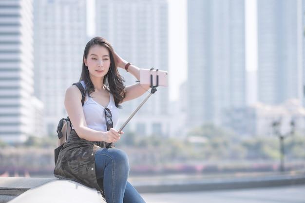 Piękna azjatykcia turystyczna kobieta bierze selfies na smartphone w miastowym miasta śródmieściu.
