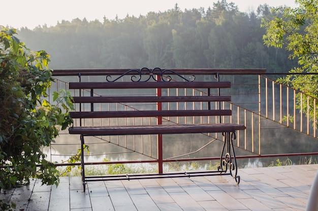 Piękna ażurowa ławka o świcie nad brzegiem jeziora latem