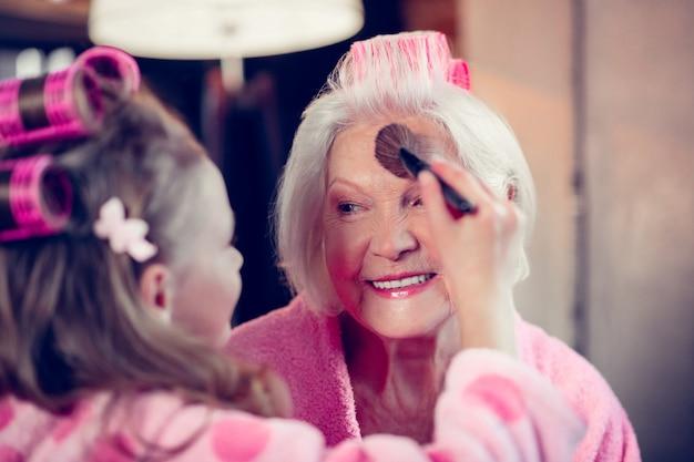 Piękna babcia. śliczna dziewczyna robi makijaż dla swojej pięknej babci, która nakłada puder do twarzy