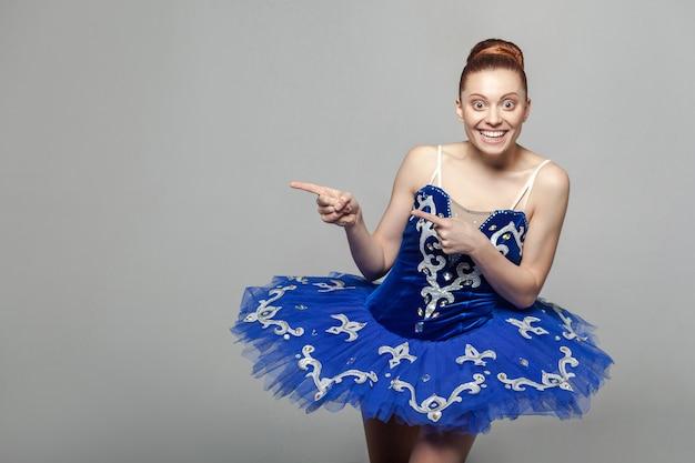 Piękna balerina kobieta stojąca na szarym tle, wskazując na ścianę i patrząca na kamerę