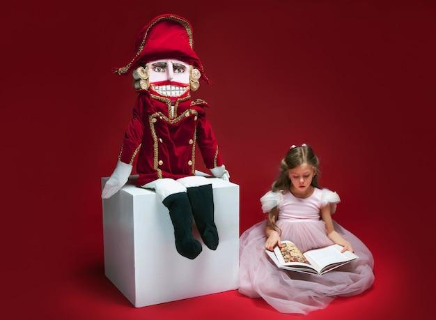 Piękna balerina siedzi w pobliżu dziadek do orzechów i czytając książkę w czerwonym studio