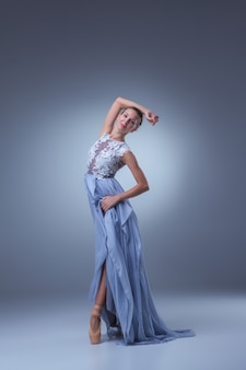 Piękna balerina tańczy w długiej niebieskiej sukience na niebieskim tle
