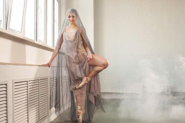 Piękna baletnica o idealnym ciele ubrana w stylową sceniczną długą przezroczystą szatę i szarą woalkę na głowie, tańczącą na tle dymu w studio