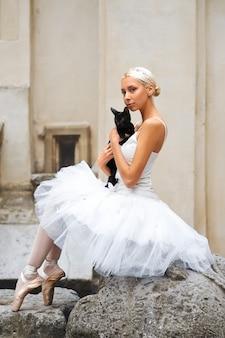 Piękna baletnica pieszcząca czarnego kota