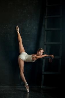 Piękna baletnica posin w ciemnym pokoju