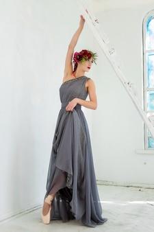 Piękna baletnica pozuje w długiej szarej sukience