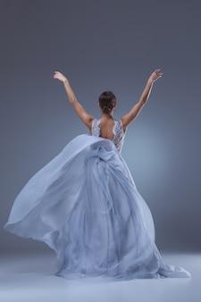 Piękna baletnica tańczy w długiej liliowej sukience na liliowym tle