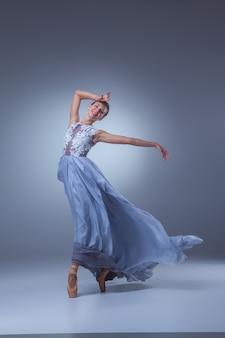 Piękna baletnica tańczy w długiej niebieskiej sukience na niebieskim tle