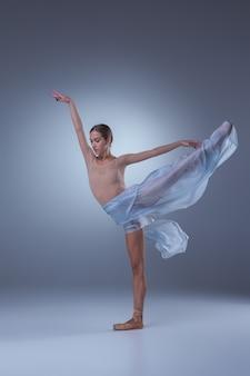 Piękna baletnica tańczy z niebieskim welonem na niebieskim tle