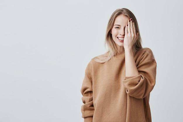 Piękna, bardzo urocza młoda blondynka w luźnym swetrze, uśmiechając się radośnie, dobrze się bawiąc w pomieszczeniu, zamykając jedno oko ręką