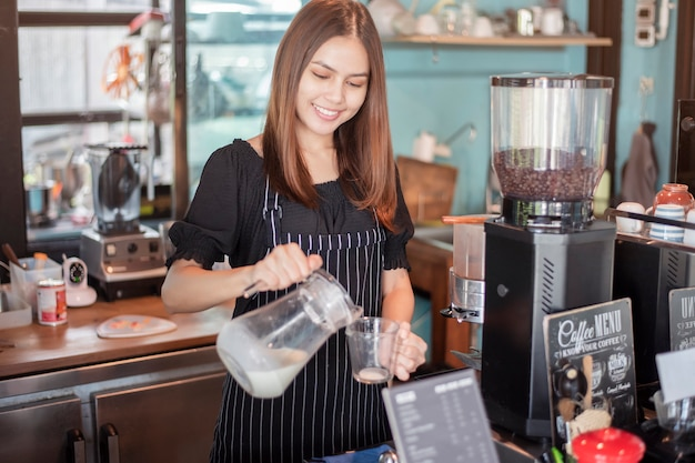Piękna barista uśmiecha się w swojej kawiarni
