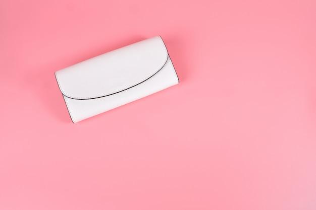 Piękna beżowa torebka ze sprzęgłem leży na różowym pastelowym tle. akcesoria dla kobiet. modny styl. połóż płasko żeński portfel