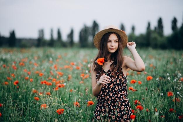 Piękna bezpłatna dziewczyna w kapeluszu w letnim polu czerwonych maków