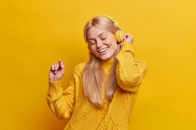 Piękna, beztroska blondynka tańczy, unosząc ramię, relaksuje się przy przyjemnej muzyce ze słuchawek