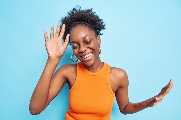 Piękna Beztroska Ciemnoskóra Kobieta Tańczy Z Uniesionymi Rękami Do Muzyki Imprezowej Zamyka Oczy Z Przyjemności Cieszy Się życiem Darmowe Zdjęcia