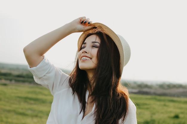 Piękna beztroska długie włosy azjatykcia dziewczyna w biel ubraniach i słomianym kapeluszu cieszy się życie w natury polu przy zmierzchem
