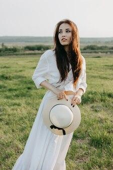 Piękna beztroska długie włosy azjatykcia dziewczyna w biel ubraniach i słomianym kapeluszu cieszy się życie w polu przy zmierzchem
