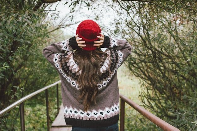 Piękna beztroska dziewczyna z długimi włosami w czerwonej czapce i dzianinowym swetrze z tyłu w jesiennym parku przyrody, przygoda w podróży