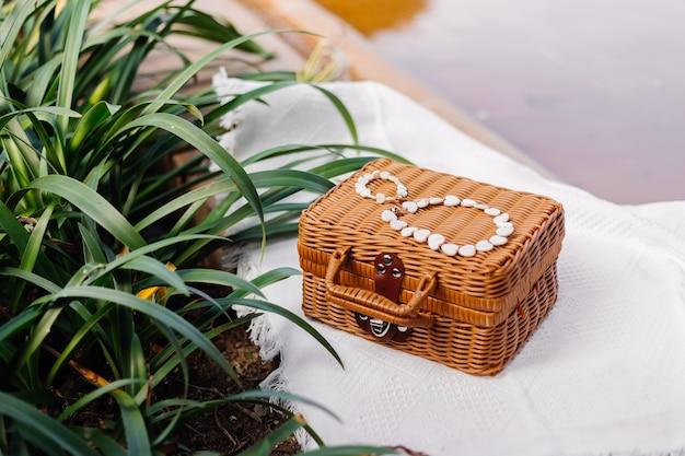 Piękna biała bransoletka i naszyjnik z muszelek na brązowej wiklinowej klatce piersiowej i białym dywanie plażowym przez tropikalne liście na zewnątrz strzał