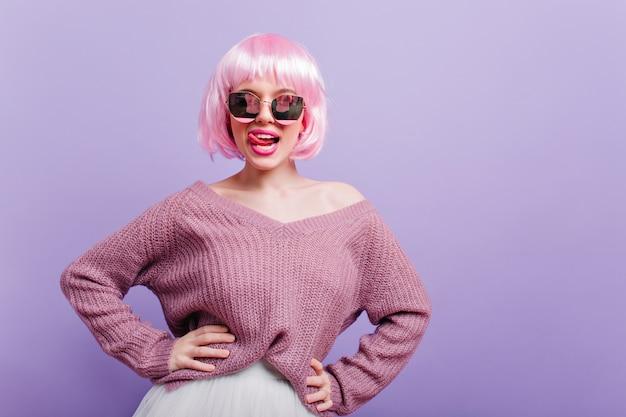 Piękna biała dziewczyna w modnej peruce zabawy podczas sesji zdjęciowej. portret szczęśliwa młoda modelka z krótkimi różowymi włosami stojąc w pewnej pozie i uśmiechając się.