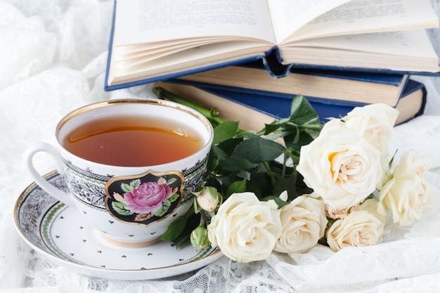 Piękna biała filiżanka herbata i wzrastał na białym tle
