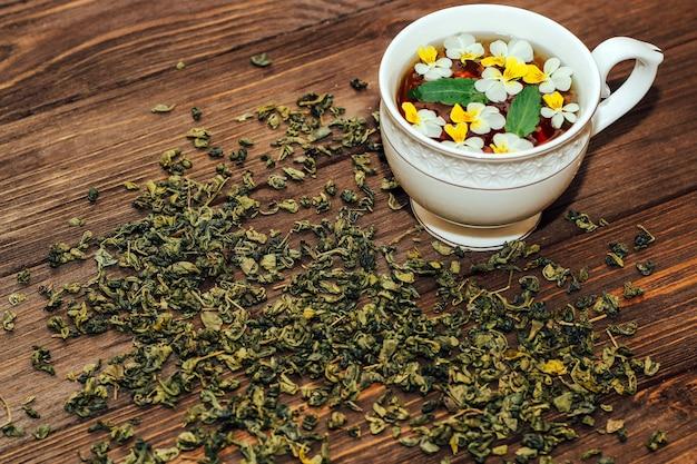 Piękna biała filiżanka ze złotą obwódką ozdobiona kwiatami, ziołową zieloną zdrową herbatą. projekt konta biznesowego.