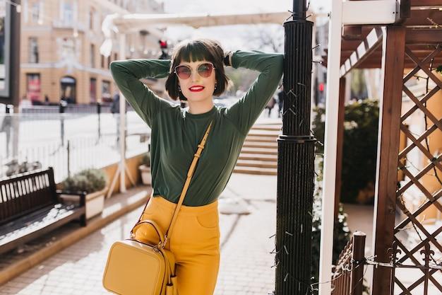Piękna biała kobieta pozuje z rękami na ulicy i wyraża zainteresowanie. zewnątrz zdjęcie uroczej czarnowłosej dziewczyny w zielonym swetrze trzymając żółtą torebkę.
