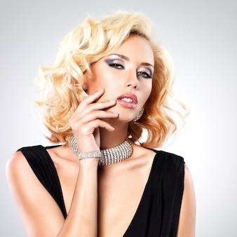 Piękna biała kobieta z kręconą fryzurą i srebrną bransoletą -