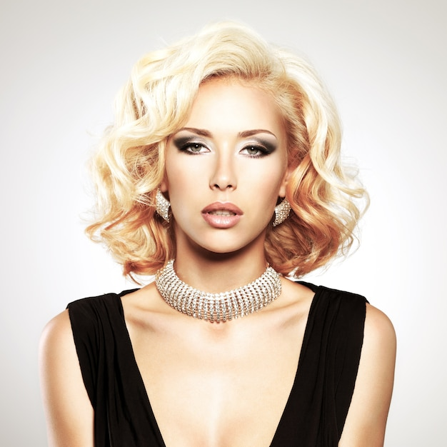 Piękna biała kobieta z kręconą fryzurą i srebrnymi zdobieniami pozowanie w studio