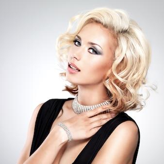 Piękna biała kobieta z kręcone fryzury, pozowanie w studio