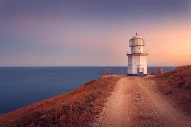 Piękna biała latarnia morska na ocean linii brzegowej przy zmierzchem