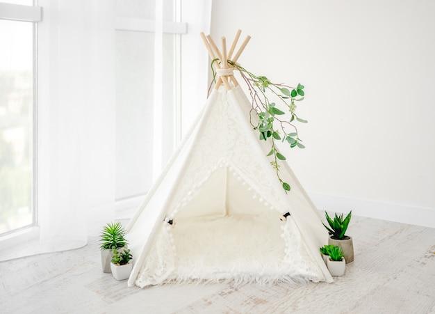 Piękna biała ozdoba chaty do sesji noworodkowej z roślinami i futrem w jasnym pomieszczeniu. stylowe meble wigwam dla niemowląt dziecko studio foto