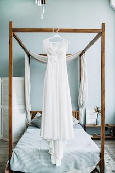 Piękna biała suknia ślubna przed łóżkiem