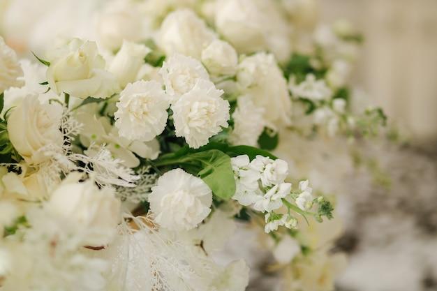 Piękna biało-zielona dekoracja kwiatowa na weselnym stole w restauracji