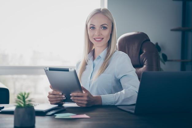 Piękna biznesowa dama trzyma uśmiech na tablecie